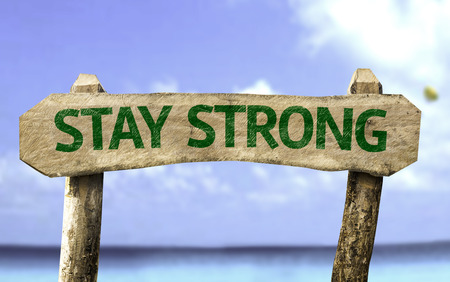 Wooden sign board with text: Stay Strong on sea background