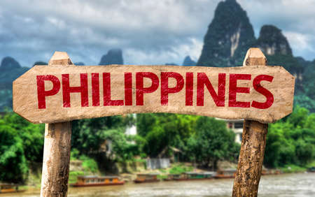 pinoy: Wooden sign board with text: Philippines on outdoors background Stock Photo