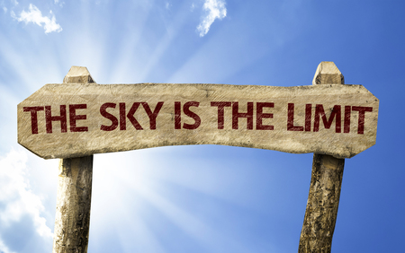 Wooden sign board on sky background with text: The Sky Is The Limit Stock Photo