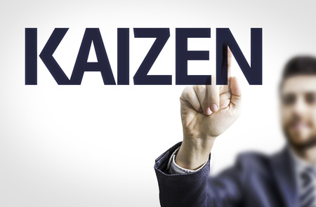 Business man pointing to transparent board with text: Kaizen