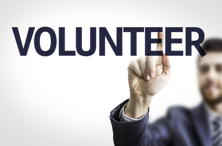Business man pointing to transparent board with text: Volunteer