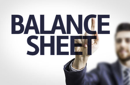Business man pointing to transparent board with text: Balance sheet