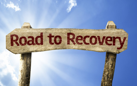 road to recovery: Road to recovery sign with sunny background