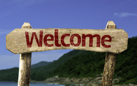 courteous: Welcome sign with beach background Stock Photo