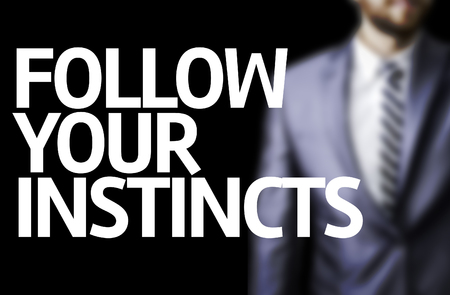 Business man in black background with the text: Follow your instincts