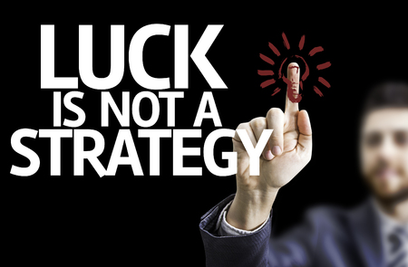black luck: Business man pointing to black board with text: Luck is not a strategy