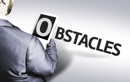 Business man in low angle view with the text: Obstacles