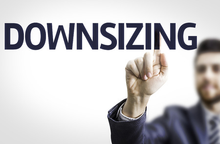 downsizing: Business man pointing to transparent board with text: Downsizing