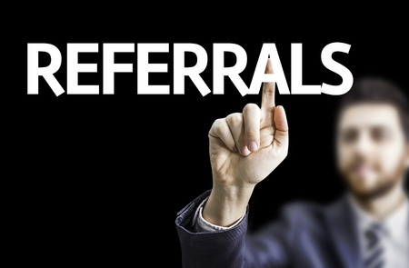 referidos: Business man pointing to black board with text: Referrals