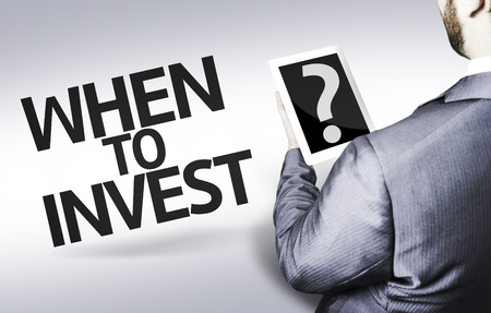 buy shares: Business man in low angle view with the text: When to invest?