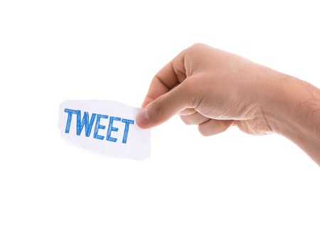 tweet: Hand holding piece of paper on white background with text: Tweet