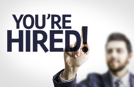 Business man pointing to transparent board with text: Youre hired!