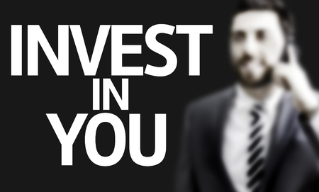 invest: Business man in black background with the text: Invest in you
