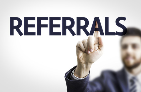 Business man pointing to transparent board with text: Referrals Stock Photo