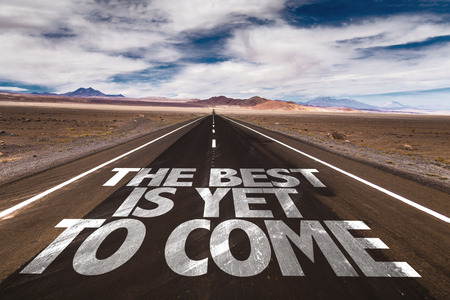 come on: The best is yet to come written on the road sign with clouds and sky background