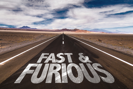 Fast & furious written on the road sign with clouds and sky background