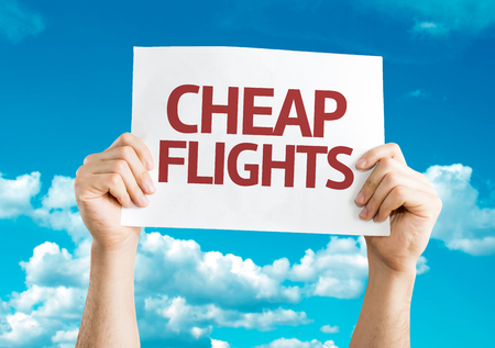Hands holding cardboard on sky background with text: Cheap flights