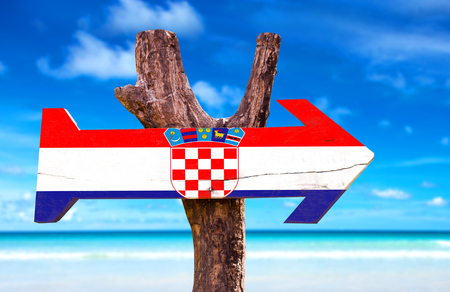 bandera de croacia: Croatia flag sign with arrow on beach background Foto de archivo