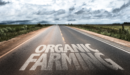 farming sign: Organic farming written on the road sign with clouds and sky background Stock Photo