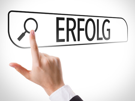 Hand searching online on white background with text: Erfolg (Success in German) Stock Photo
