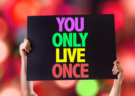 cardboard only: Hands holding cardboard on bokeh background with text: You only live once Stock Photo