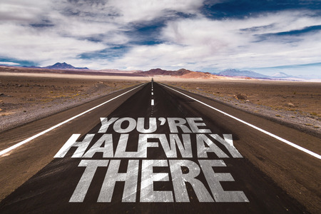 Youre halfway there written on the road sign with clouds and sky background Stock Photo