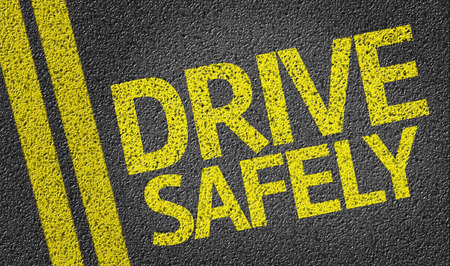 safely: Text on tar road: Drive safely Stock Photo