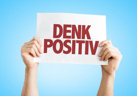 positiv: Hands holding cardboard on blue background with text: Denk positiv (Think positive in German)
