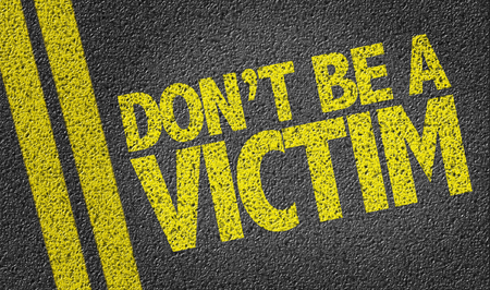 intimidated: Text on tar road: Dont be a victim Stock Photo