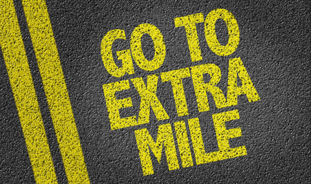 mile: Text on tar road: Go to extra mile