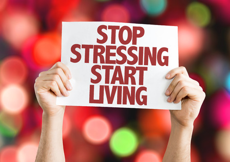 stressing: Hands holding cardboard on bokeh background with text: Stop stressing start living Stock Photo