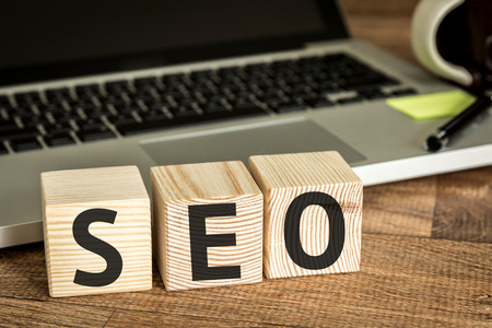 page rank: SEO written on a wooden cube with laptop background
