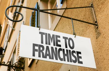 Time to franchise signpost on building background Stock Photo