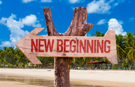 new beginning: New beginning sign with arrow on beach background