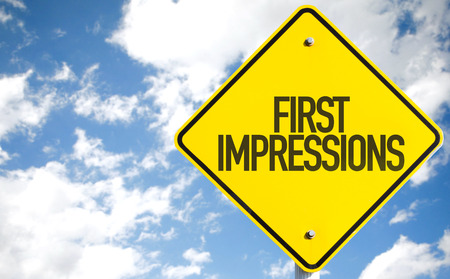 First impressions sign with clouds and sky background