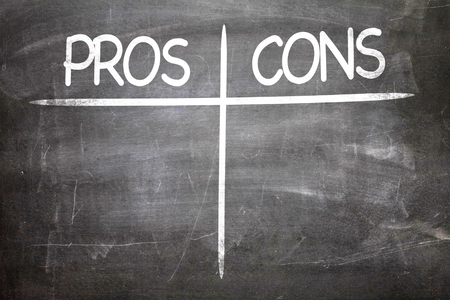cons: Pros cons written on blackboard
