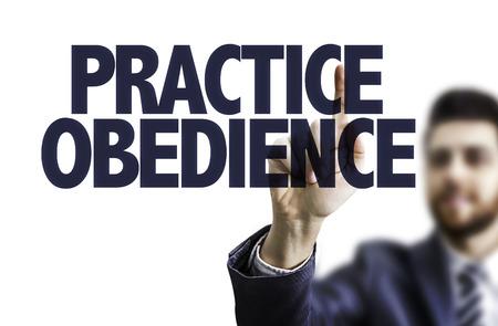 obedience: hombre de negocios apuntando hacia el tablero transparente con el texto: la obediencia Práctica Foto de archivo