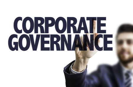 corporate governance: Business man pointing to transparent board with text: Corporate governance