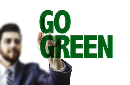 Business man pointing to transparent board with text: Go green