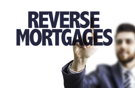 reverse: Business man pointing to transparent board with text: Reverse mortgages Stock Photo
