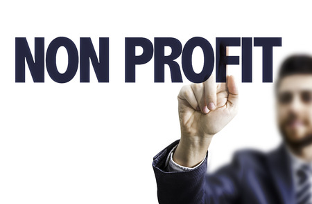 non profit: Business man pointing to transparent board with text: Non profit Stock Photo