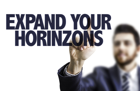 expand: Business man pointing to transparent board with text: Expand your horizons Stock Photo