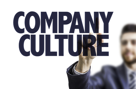 Business man pointing to transparent board with text: Company culture