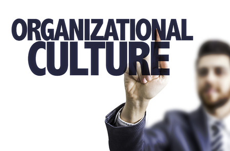 Business man pointing to transparent board with text: Organizational culture Archivio Fotografico
