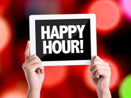 hands  hour: Hands holding tablet pc on bokeh background with text: Happy hour! Stock Photo