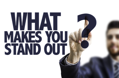 Business man pointing to transparent board with text: What makes you stand out?
