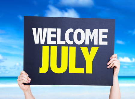Hands holding cardboard on beach background with text: Welcome July