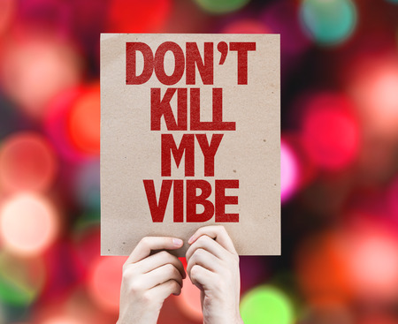 Hands holding cardboard on bokeh background with text: Dont kill my vibe Stock Photo