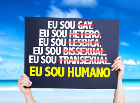 sou: Hands holding cardboard on beach background with text: Eu sou humano (I am human in Portuguese) Stock Photo