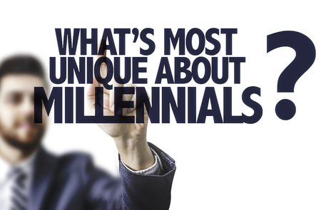 Business man pointing to transparent board with text: What's the most unique about millennials?